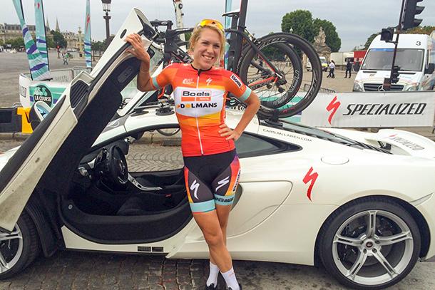 Ellen van Dijk posing happily on front of a McLaren sportscar | Racefietsblog.nl
